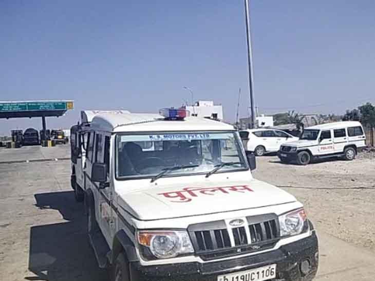 जोधपुर-नागौर रोड पर खड़े पुलिस के वाहन और टोल नाके से निकलते ट्रक।