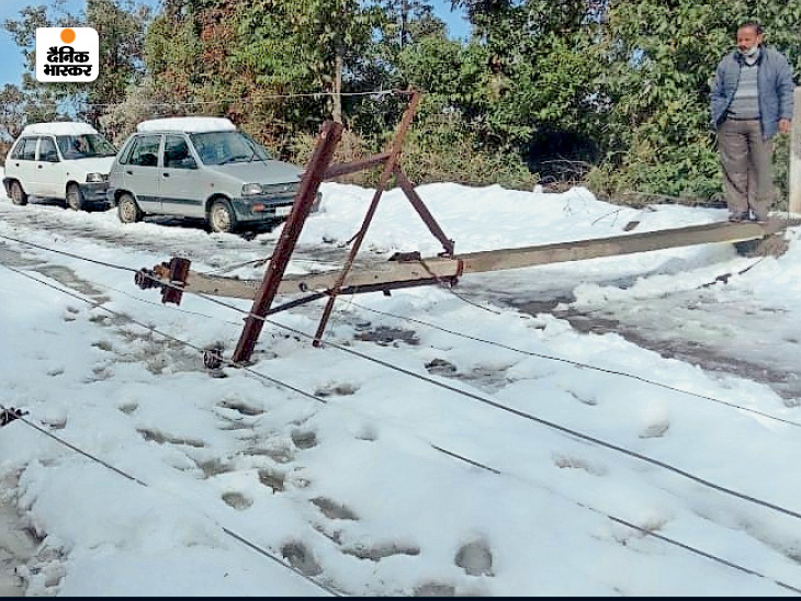 A fallen electric pole on the road after snowfall in Shimla.