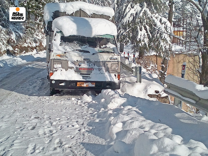 A truck driver had to park his truck on the side of the road due to snowfall.