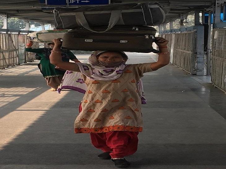 ट्रेन रुकने के बाद बैग लेकर बस स्टैंड के लिए जाती महिला।