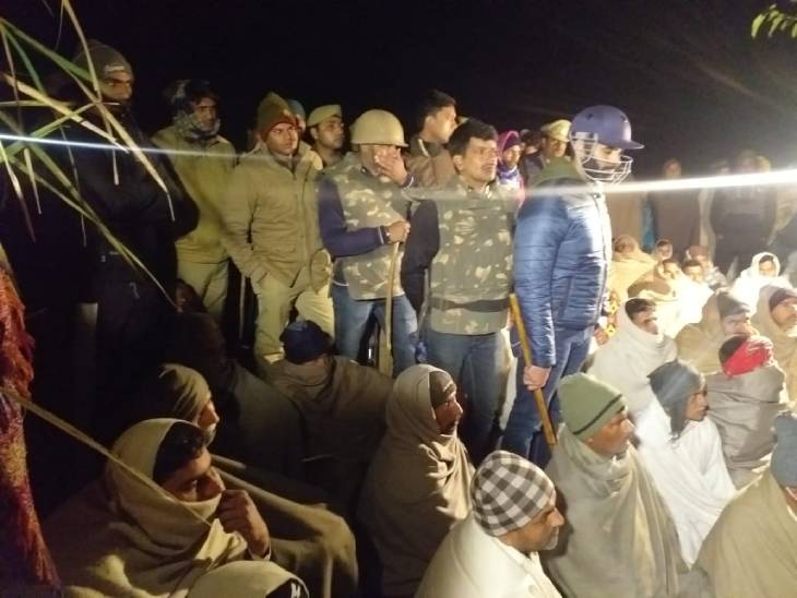 Villagers and police gathered on a dharna in the field.