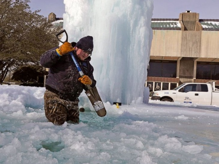 टेक्सास में फव्वारा तक जम गया है। फव्वारे के पास जमे बर्फ को हटाने की कोशिश करता कर्मचारी।