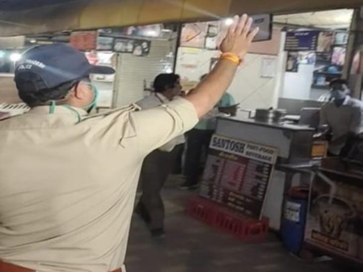 रात 10 बजे इंदौर में 56 दुकान एरिया को बंद कराता पुलिस का जवान।
