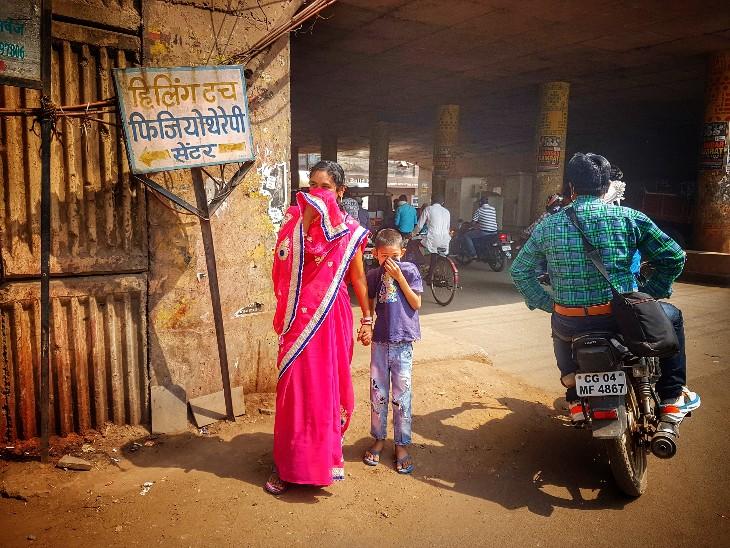 चेकिंग का माहौल देखकर, अपनी मां के साथ रास्ते से गुजर रहे इस बच्चे ने भी मुंह ढंक लिया- तस्वीर रायपुर की।