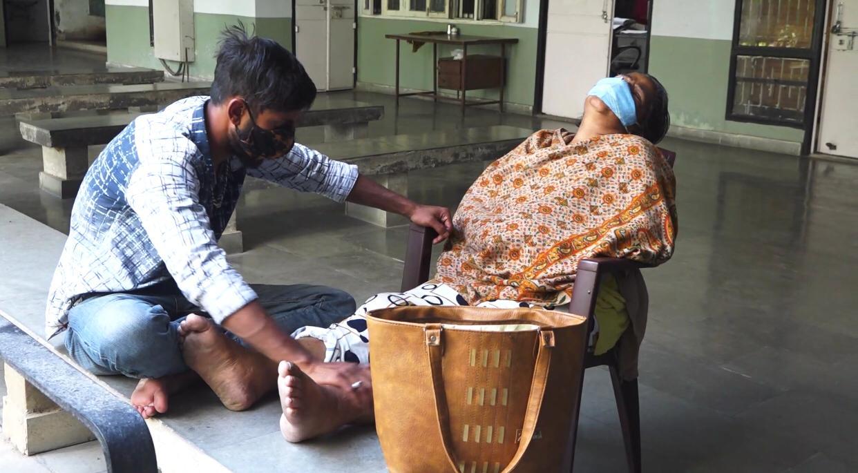 डायलसिस न होने से दर्द से तड़फती महिला के पैर दबाता परिजन।