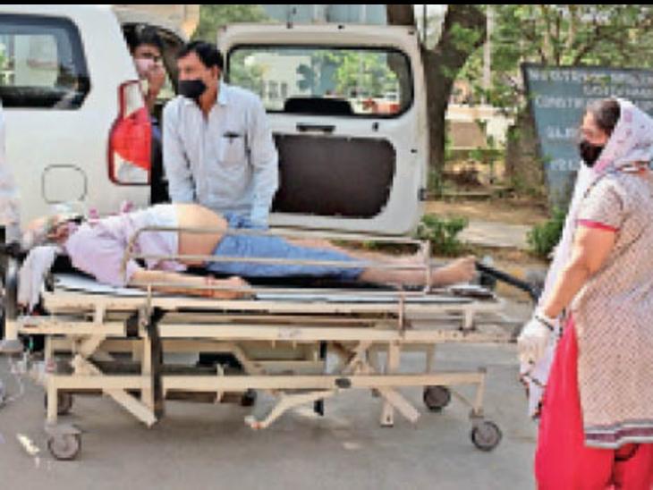 कोरोना संक्रमित मरीज को गंभीर हालत में ऑक्सीजन सिलेंडर सहित भर्ती कराने ले जाते परिजन व अस्पताल कर्मी।