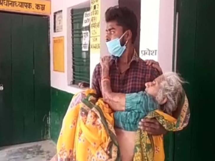 कानपुर के बिकरु गांव में बुजुर्ग महिला को गोद में लेकर मतदान केंद्र पहुंचा युवक।