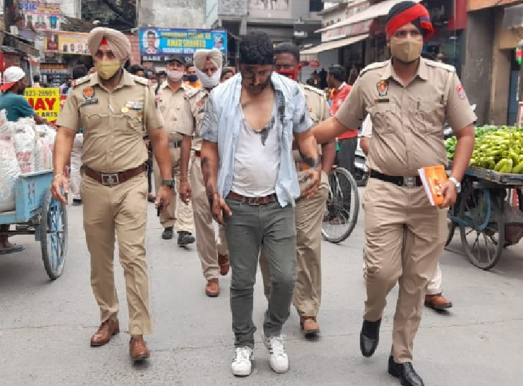 आरोपी अध्यापक को बीच बाजार से लेकर जाती पुलिस।