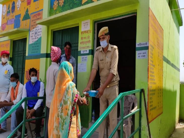 प्राथमिक विद्यालय मलहियां में पुलिस वाला वोटरों के हाथों में सैनिटाइजर देता हुआ।