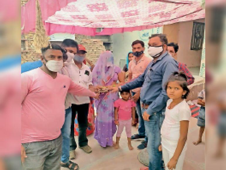 भरतपुर. पीड़िता परिवार को आर्थिक सहायता देते कर्मी। - Dainik Bhaskar
