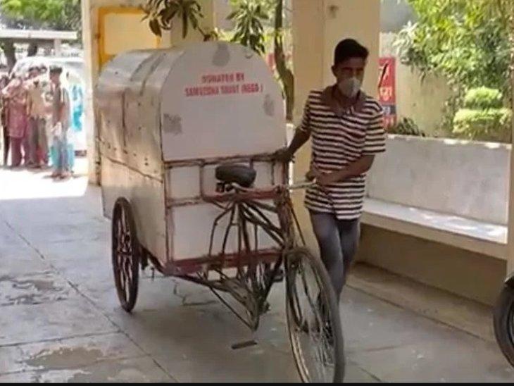 बुग्गी रिक्शा में मां का शव लेकर श्मशान पहुंचा युवक।