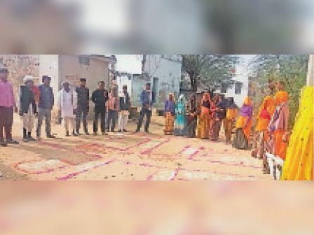 दौसा ग्रामीण स्वच्छ भारत मिशन के तहत मॉडल गांव चुनने पर गुगोलाव में रंगोली बनाकर मॉडल गांव की जानकारी देते अधिकारी। - Dainik Bhaskar