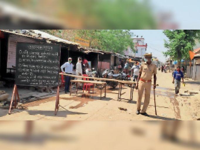 देवरी. कस्बे के मुख्य बाजार में लगाए गए बेरिकेड्स व बोर्ड पर लिखी सूचना। - Dainik Bhaskar