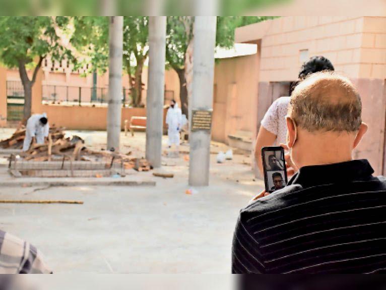 हिसार   ऋषि नगर श्मशान घाट में दिल्ली का रहने वाला एक व्यक्ति वीडियो कॉल कर परिजनों को कोविड पेशेंट की मौत के बाद अंतिम संस्कार दिखाता हुआ है। }फोटो: रॉकी कुमार