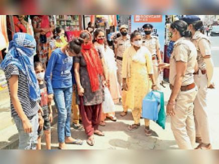 बाजार में महिलाओं को कोरोना गाइड लाइन का पालन करने के बारे में जागरुक करतीं पुलिस अधिकारी। - Dainik Bhaskar