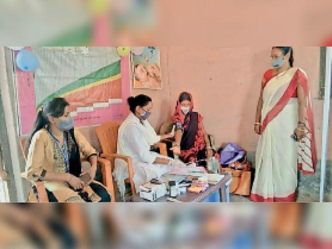 मॉडल केंद्र पर महिला की जांच करते स्वास्थ्य कर्मी। - Dainik Bhaskar