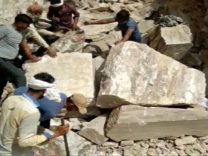 चट्टान के नीचे दबे मजदूर को निकालते मौके पर मौजूद लोग।