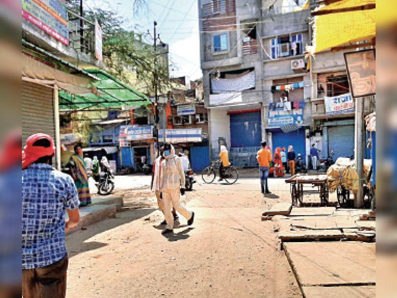 दमोह  बरंडा के सामने कपड़ा व्यवसायी शटर बंद कर ग्राहकों को सामान बेच रहे हैं। - Dainik Bhaskar