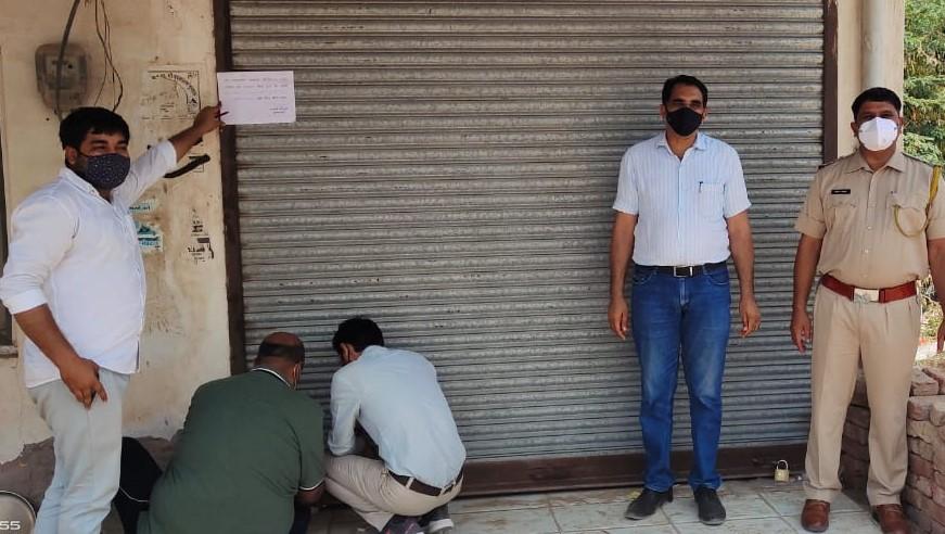 लूणकरनसर में दुकान सील कराते अधिकारी। फोटो : रामप्रताप गोदारा