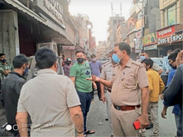 रेलवे रोड पर दुकानें बंद कराने को समझाते सिटी थाना प्रभारी राकेश सैनी। - Dainik Bhaskar