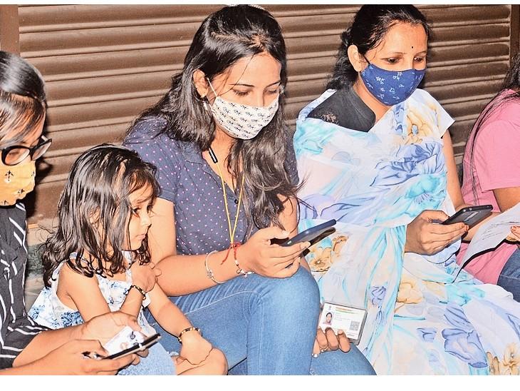 बजरंग चौक पर वैक्सीनेशन के लिए रजिस्ट्रेशन करती युवतियां। - Dainik Bhaskar
