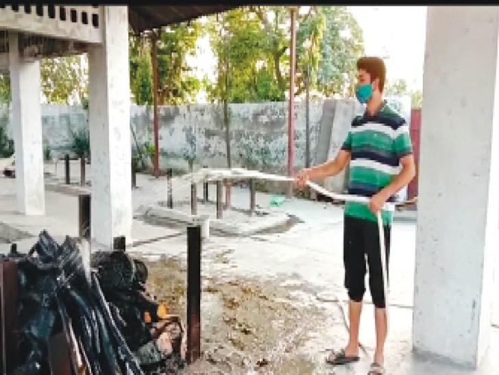 पानी डालकर चिता की आग को बुझाता मृतका का रिश्तेदार। - Dainik Bhaskar