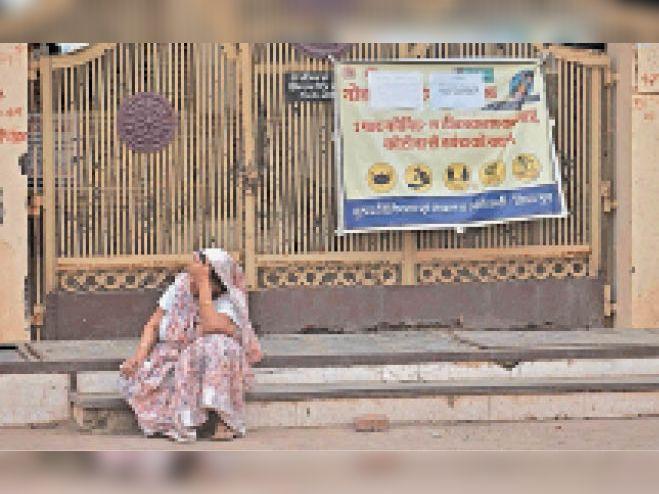कोरोना वैक्सीनेशन कराने मानस भवन पंहुची बुजुर्ग महिला दोपहर की गर्मी से परेशान होकर बंद गेट के बाहर ही बैठ गई। - Dainik Bhaskar