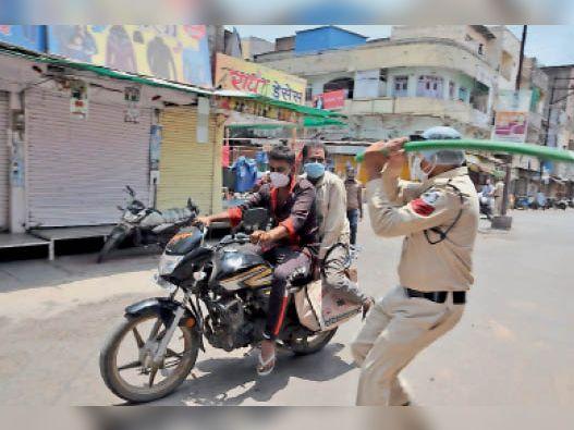 माणकचौक क्षेत्र में मोटर साइकिल पर घूमते युवक रोकने पर नहीं रुके तो पुलिसकर्मी को डंडा उठाकर सामने आना पड़ा।  फोटो   चिंटू मेहता - Dainik Bhaskar