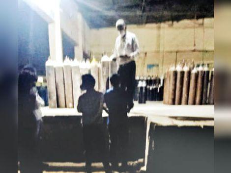 रात को फिलिंग सेंटर पर सिलेंडर फिल करते कर्मचारी। - Dainik Bhaskar