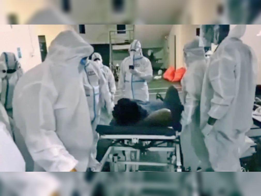 कोविड अस्पताल में पीपीई किट पहनकर संक्रमित को अस्पताल में भर्ती कराते समाज सेवी। - Dainik Bhaskar