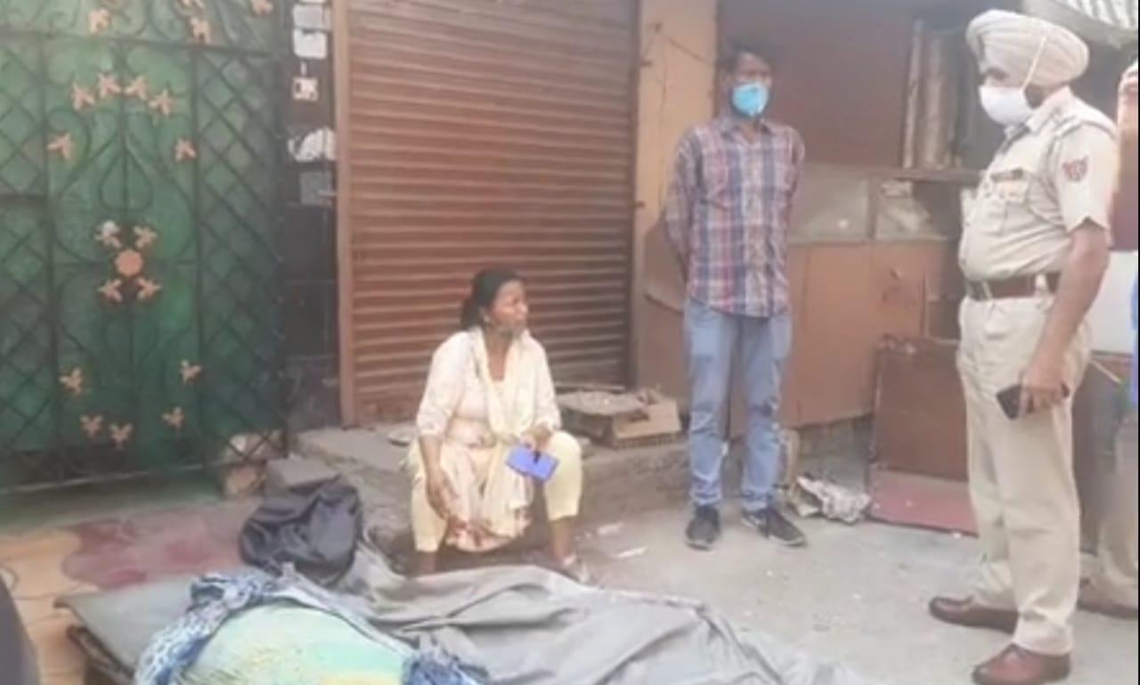 घर के बाहर शव रखकर बैठे परिजनों को समझाती पुलिस।