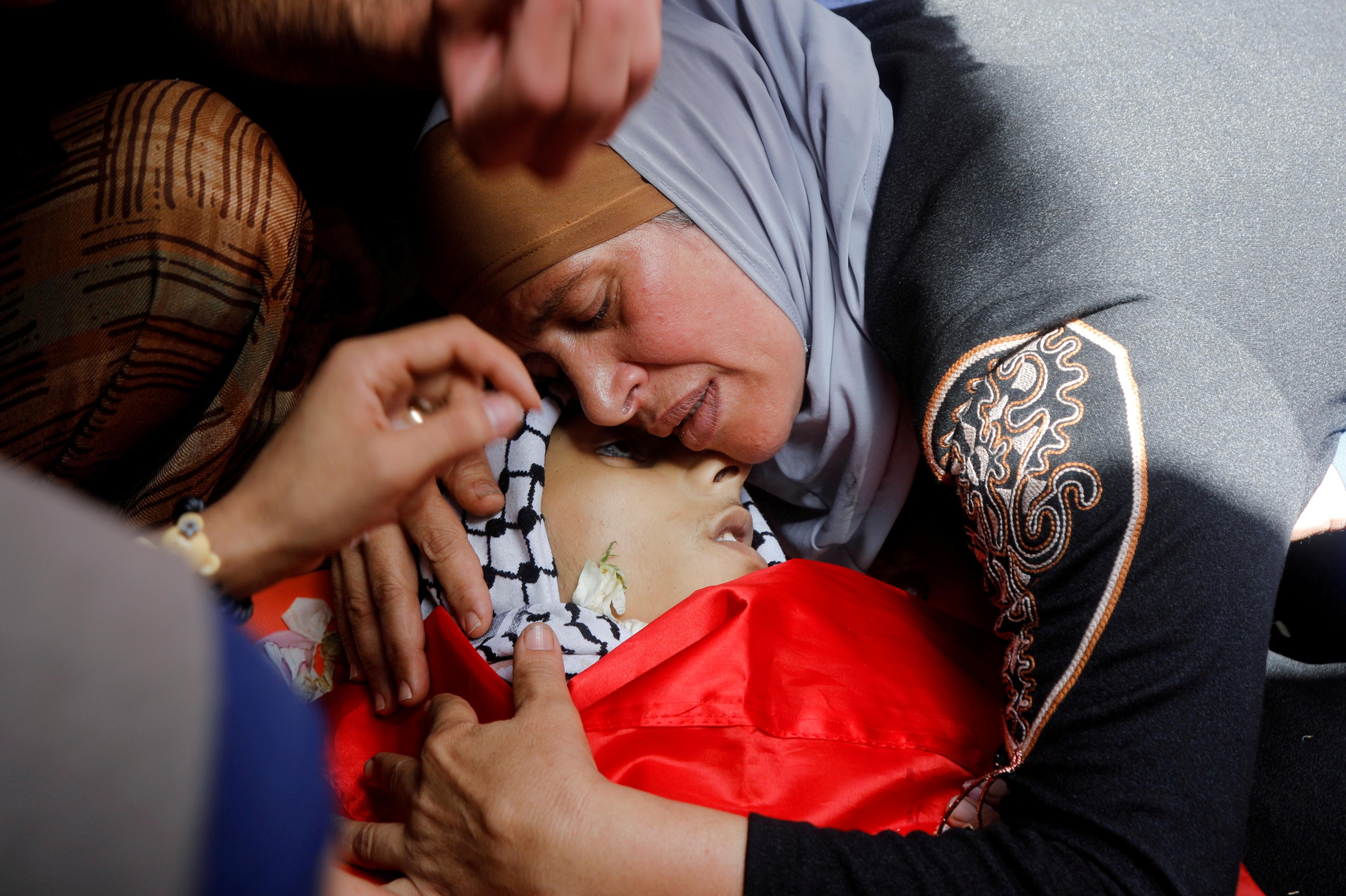 हमले में मारे गए अपने बच्चे की मौत का दुख मनाती महिला।