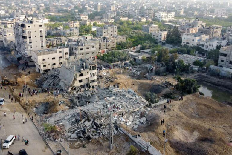 इजराइली एयरफोर्स की एयर स्ट्राइक में बर्बाद हुई बिल्डिंग को देखते स्थानीय लोग। इजराइल ने दावा किया है कि उसकी एयरस्ट्राइक में हमास के कई कमांडर मारे गए हैं।