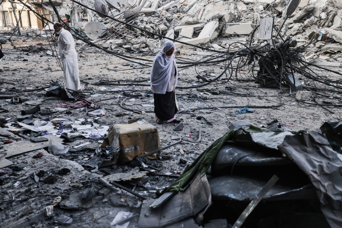 फिलिस्तीन के गाजा पट्टी में इजराइल ने सबसे ज्यादा एयर स्ट्राइक कीं। ऐसी ही एक एयरस्ट्राइक में तबाह हुए शाहरूक टावर के मलबे को देखते स्थानीय लोग।