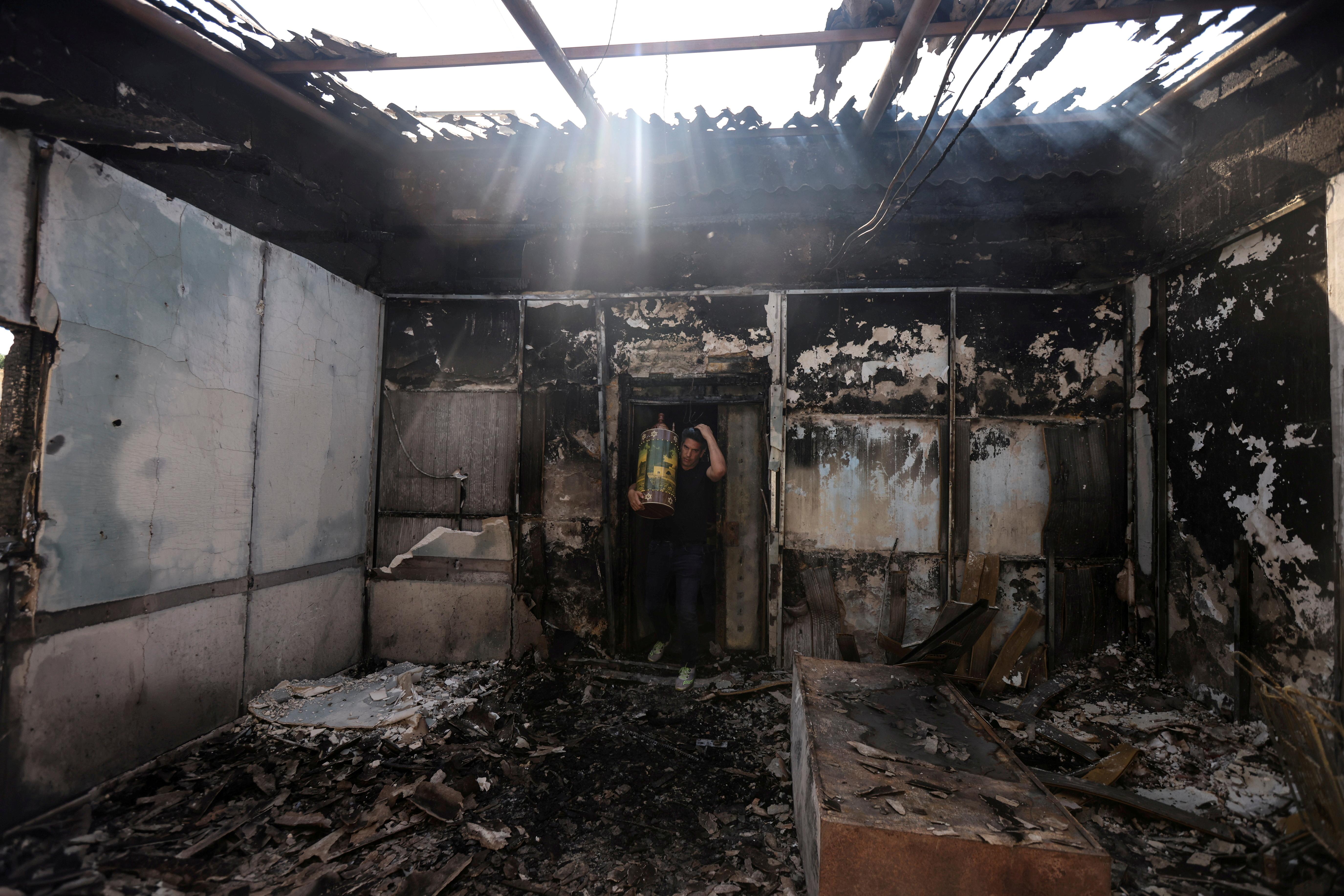 यरूशलम में हुए दंगों में यहूदियों के एक धार्मिक स्थल को आग के हवाले कर दिया गया। इसके बाद वहां से जरूरी सामान ले जाता एक युवक।