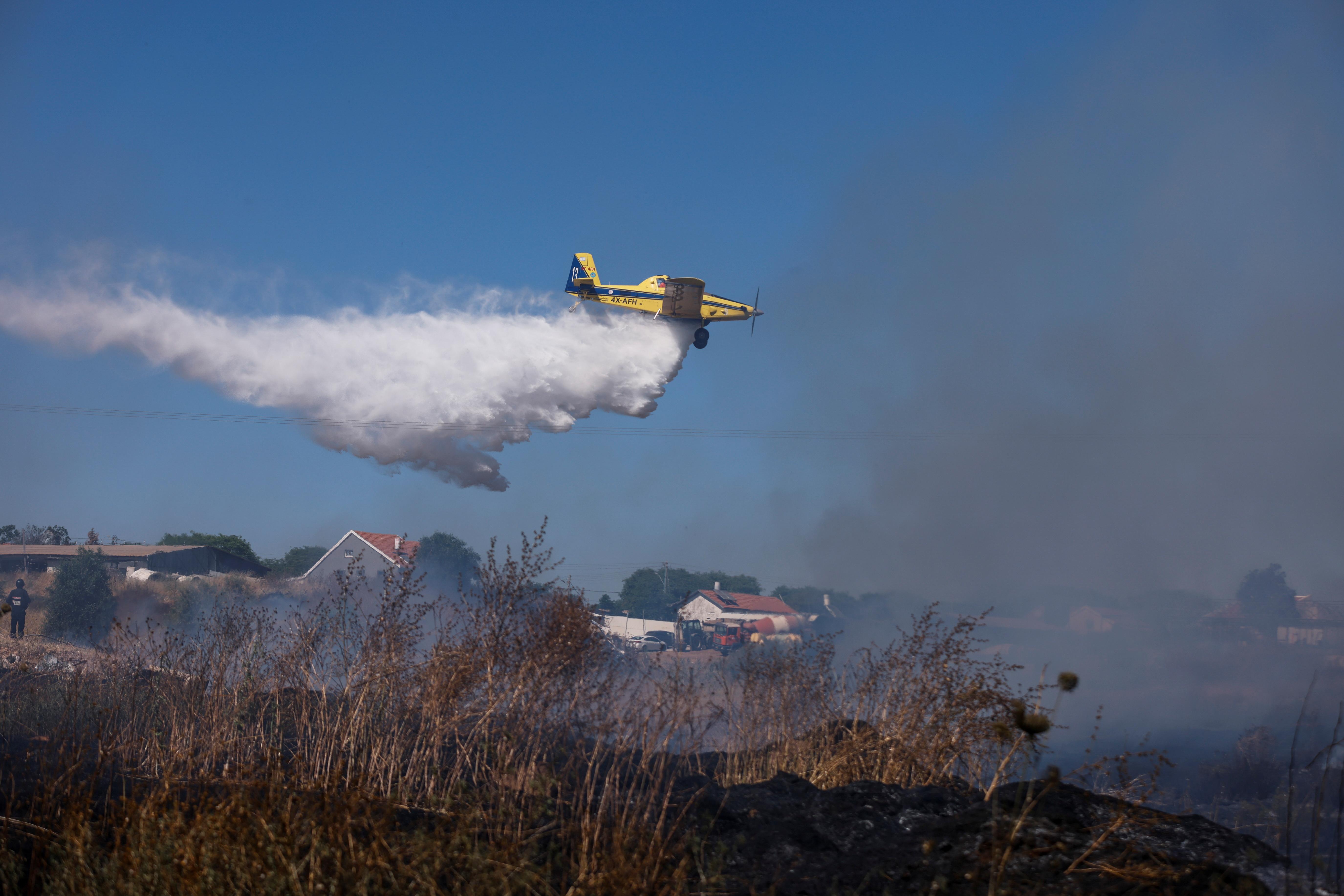 गाजा पट्टी से दागे गए रॉकेट के बाद लगी आग को बुझाने के लिए पानी की बरसात करता इजराइली एयरफोर्स का फाइटर प्लेन।