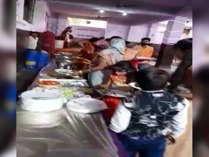 सांईकृपा मैरिज गार्डन में संक्रमण के बुफे में लाइन लगाकर खाने के लिए खड़े लोग।