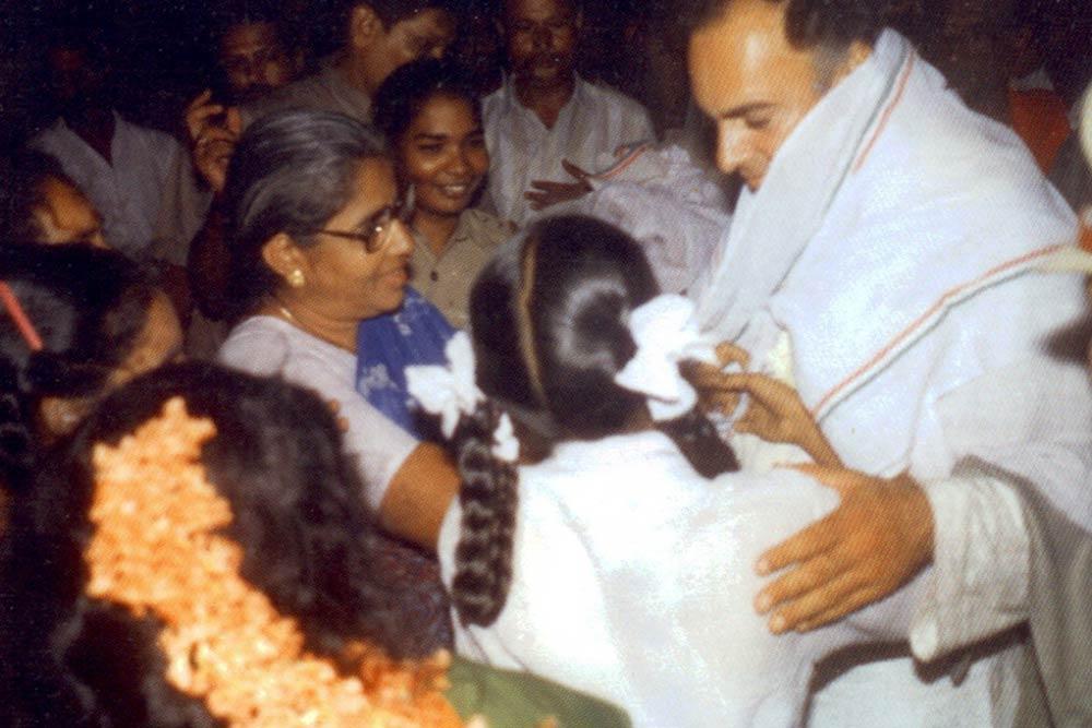 आत्मघाती हमले से पहले खींची गई राजीव गांधी की आखिरी तस्वीर। स्कूली बच्ची के पीछे नारंगी फूल सिर में लगाकर आगे बढ़ रही धनु ने ही फूलों का हार पहनाकर विस्फोट किया था।