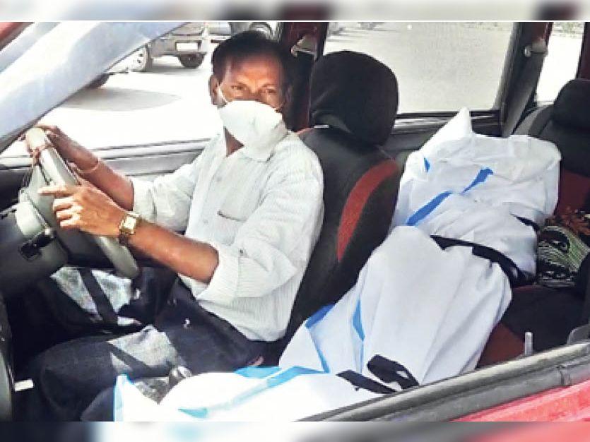पिता कार की आगे की सीट पर शव को सीट बेल्ट से बांधकर झालावाड़ लाते हुए। - Dainik Bhaskar