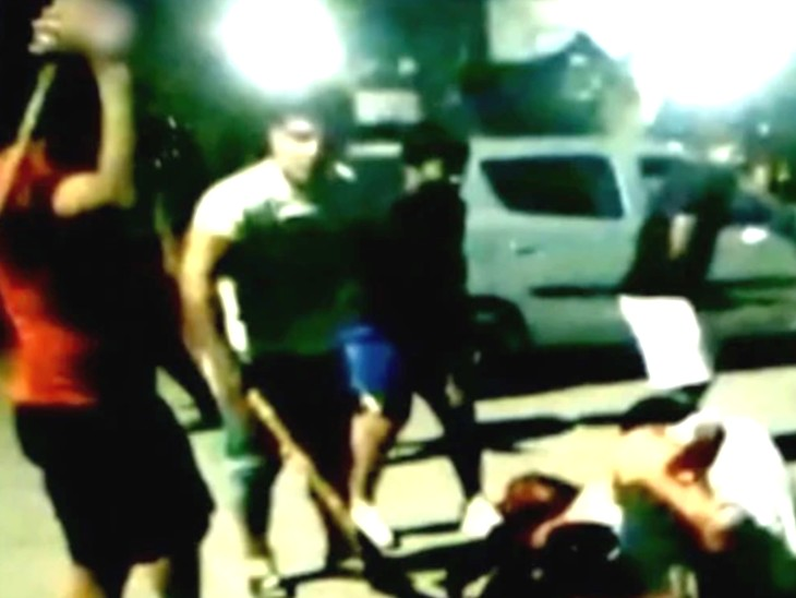 व्हाइट टी-शर्ट में ओलिंपियन सुशील कुमार दोस्तों के साथ हॉकी स्टीक से सागर की पिटाई करते हुए।
