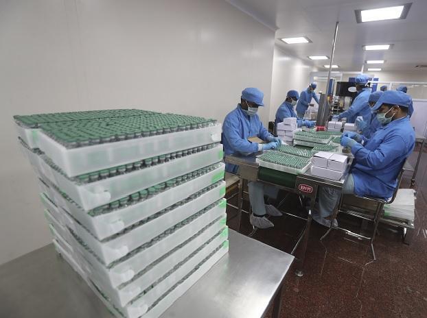 पुणे में सीरम इंस्टीट्यूट ऑफ इंडिया की फेसिलिटी में कोवीशील्ड वैक्सीन की वायल्स से भरे बक्से पैक करते हुए कर्मचारी। सीरम में 75 करोड़ डोज अगस्त से दिसंबर तक बनने की उम्मीद है, पर कंपनी की क्षमता 50 करोड़ डोज बनाने की है।