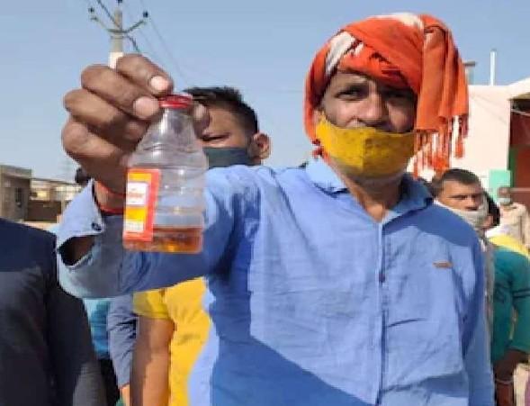 जहरीली शराब की बोतल दिखाते गांव के लोग।