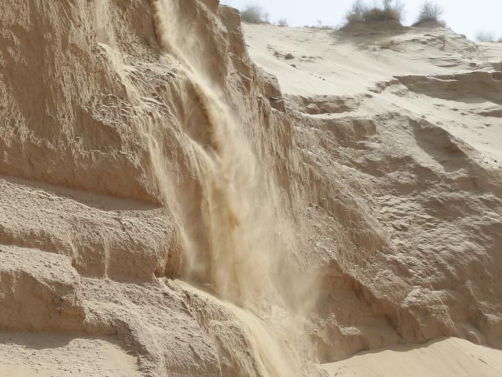 टीलों से बहता रेत का झरना।