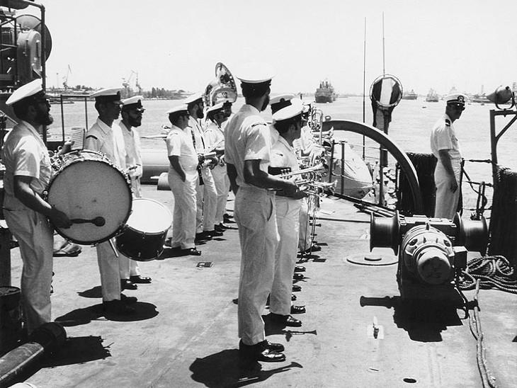 स्वेज नहर को दोबारा खोले जाने के मौके पर आयोजित कार्यक्रम में अमेरिका के लिटिल रॉक जहाज पर खड़े बैंड के सदस्य।