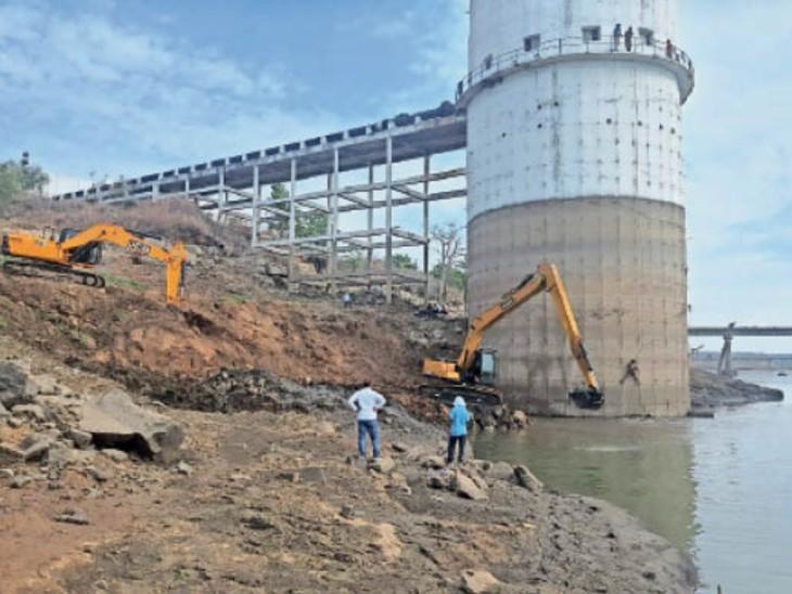चारखेड़ा में इंटकवेल तक पहुंचने के लिए एक पोकलेन से पत्थर उखाड़े जा रहे हैं और दूसरी से रास्ता बनाने के लिए पानी में पत्थर बिछाए जा रहे हैं। - Dainik Bhaskar