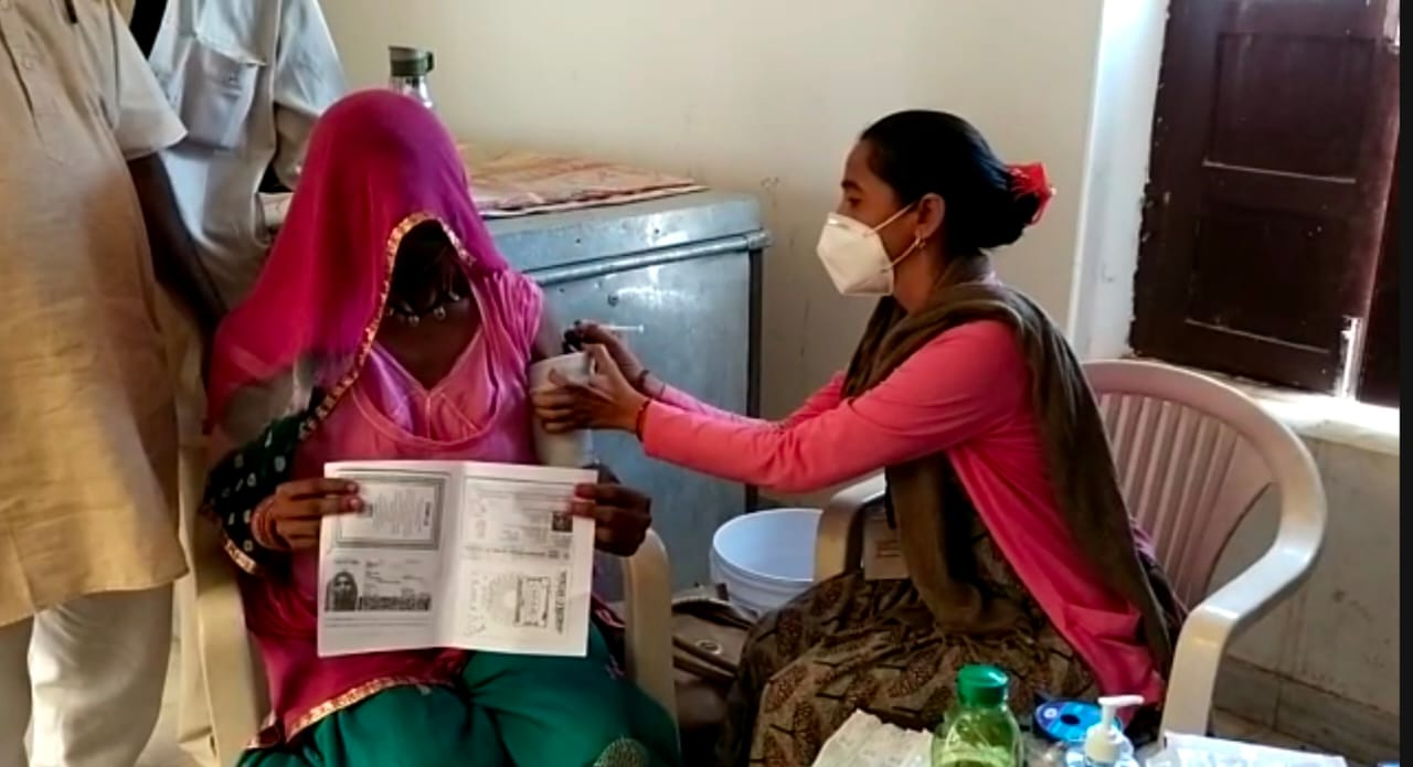 पाक विस्थापित महिला को टीका लगाती स्वास्थ्यकर्मी