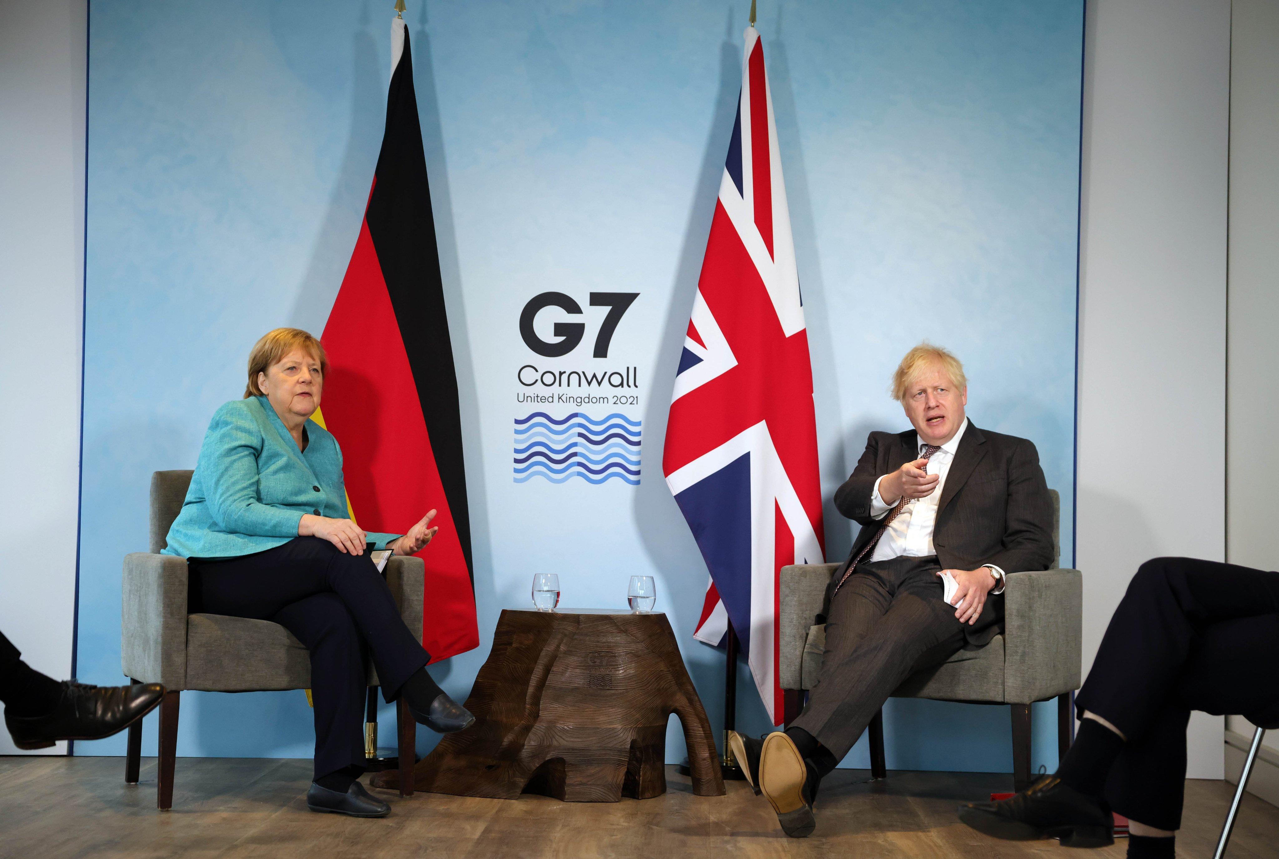 जर्मनी की चांसलर एंजेला मर्केल से चर्चा करते ब्रिटेन के प्रधानमंत्री बोरिस जॉनसन।