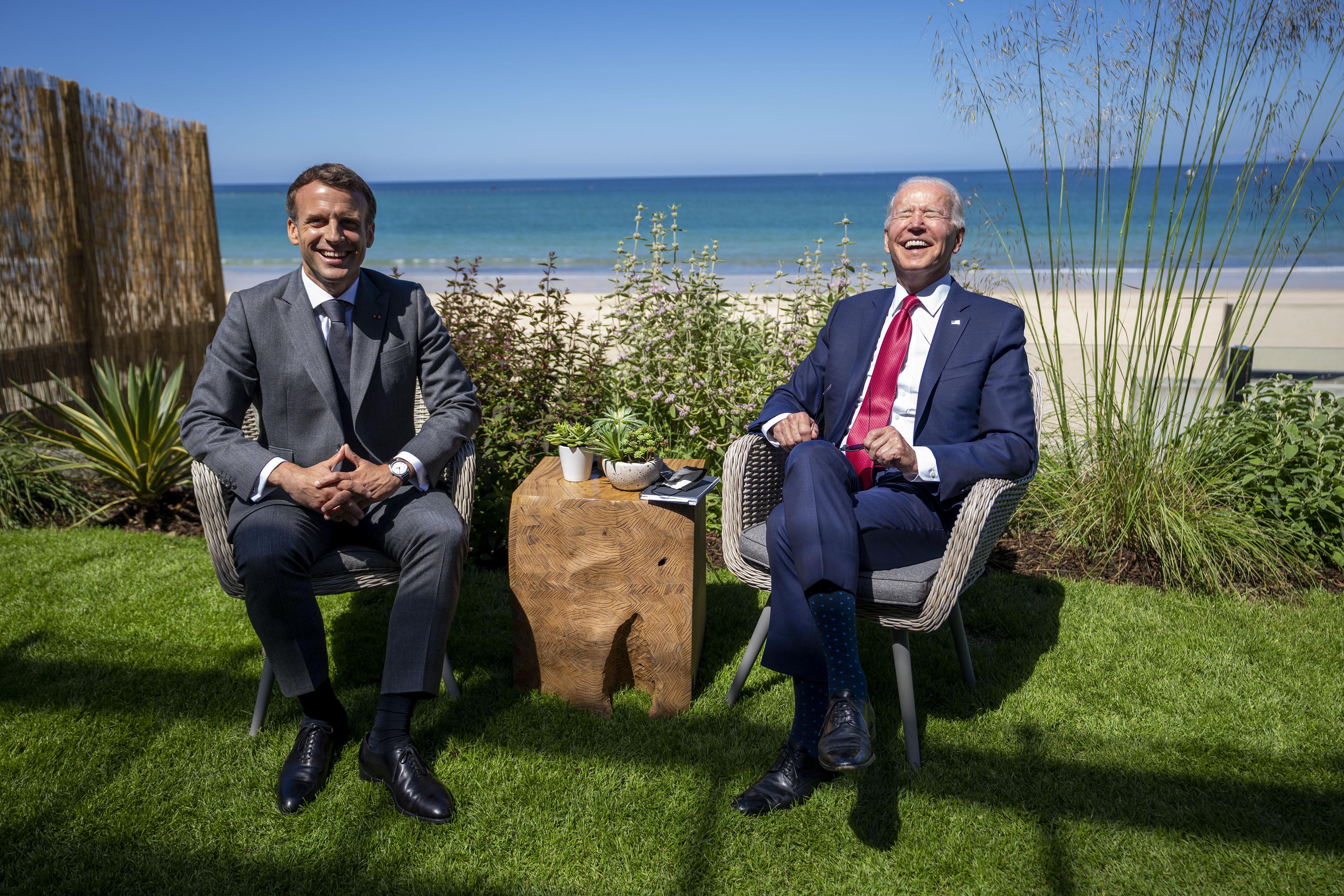 समिट के बाद बीच के किनारे बैठकर बातचीत करते फ्रांस के राष्ट्रपति इमैनुएल मैक्रों और US प्रेसिडेंट जो बाइडेन।