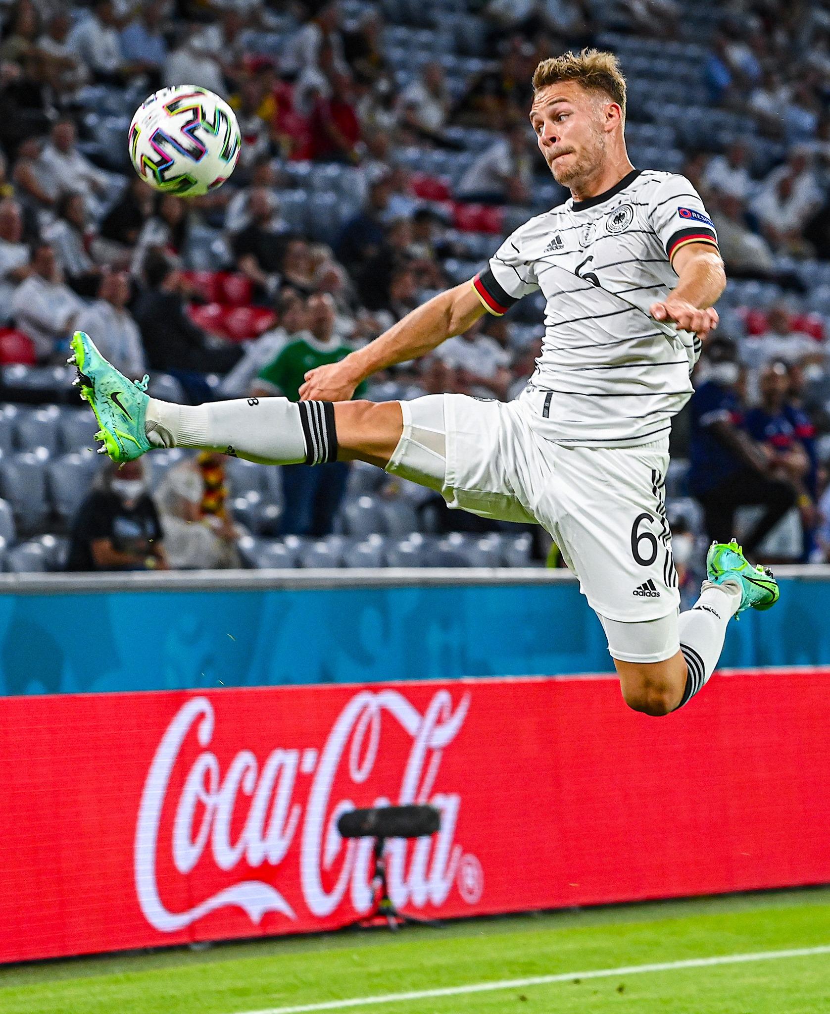मैच के दौरान जर्मनी के खिलाड़ी जोशुआ किमिच गेंद को कंट्रोल करने की कोशिश में।