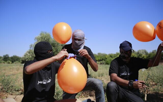 फिलिस्तीन के इस्लामिक जिहाद ग्रुप के लोग इजराइल पर विस्फोटक पहुंचाने के लिए गुब्बारे तैयार करते हुए।